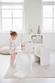 Kleines Mädchen am Spieltisch im Kinderzimmer ganz in Weiß