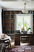Dark desk in front of old books in bookcase in study