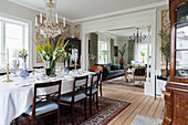 Set dining table in classic dining room with open doorway leading into living room