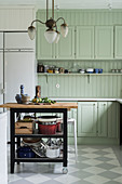 Serving trolley in mint-green country-house kitchen with chequered floor