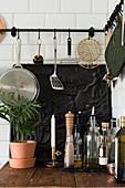 Kitchen utensils hung from hook rails above cast-iron, decorative fireback plate