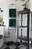 Grey display cabinet and heated towel rail in classic bathroom