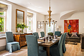 Blue loose-covered chairs around set dining table in classic interior
