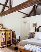 Vintage-style dolls' house in bedroom with exposed roof structure