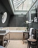 Modernes Bad in Beige und Grau mit Bullauge und Glasdach