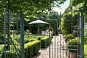 View through garden gate into classic, English-style garden