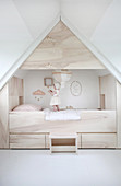 Child standing on modern cubby bed surrounded by storage in attic bedroom