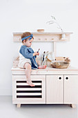Little girl sitting on pale wooden play kitchen