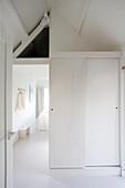 Sliding door leading into white attic bedroom