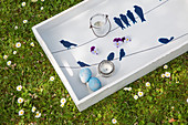 White wooden tray decorated for Easter with blue bird motifs