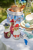 Smoothies, bread basket and crockery on table set for Easter breakfast in garden