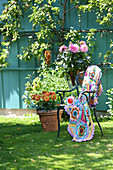 Multi-coloured crocheted blanket on chair on lawn in garden