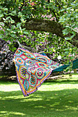 Multi-coloured crocheted blanket on hammock hung below tree
