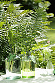 Fern fronds in glass bottles decorated with fern-shaped wooden pendants