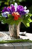 Posy of sweet peas and lady's mantle leaves in silver vase