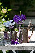 Posies of sweet peas and asparagus in silver coffee pots
