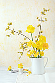 Narcissus and flowering branches of cornelian cherry in old jug