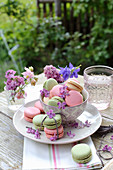 Lilacs and aquilegia in small glasses and macarons decorated with lilac flowers