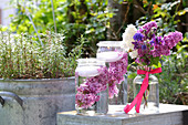 Bouquet of lilac and aquilegia next to candle lanterns made from preserving jars filled with water, lilacs and floating candles
