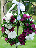 Wreath of clematis 'Mme Julia Correvon' and rose 'Snow Ballet' tied to a heart-shaped decorative stake