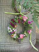 Small wreath of flowers on the zinc bucket