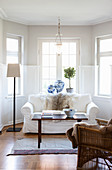 White sofa and wicker chair in classic living room with window bay
