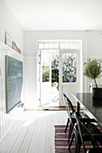 Black table in white dining room with double doors leading to garden