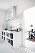 White, masonry kitchen base units with integrated gas hob and view into dining room