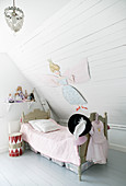 Vintage-style bed below sloping ceiling in child's bedroom