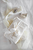Gift wrapped in patterned white fabric and tied with fabric ribbon