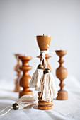 Selbstgemachte Quasten an gedrechselten Kerzenständern aus Holz