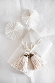 Gift wrapped in white decorated with handmade tassel