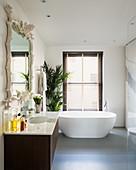 Maritime mirror and free-standing bathtub in elegant bathroom
