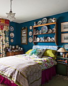 Collection of crockery on plate rack on blue bedroom wall