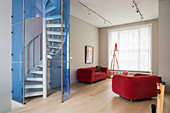 Spiral staircase with blue glass wall and red sofa in living room