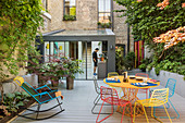 Colourful metal furniture in seating area on summery courtyard terrace