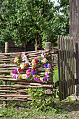 House number made from wreaths of flowers hung on wattle fence
