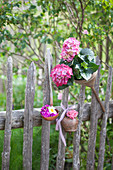 Rusty kitchen utensils decorating garden fence and hydrangeas in old funnel