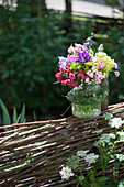 Bouquet in preserving jar with grass braid on top of wattle fence