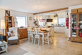 Dining table and open-plan kitchen in large, country-house-style interior