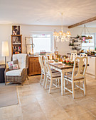 Festively set dining table in open-plan, country-house-style interior