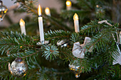 Real candles, electric candles and silver baubles on Christmas tree