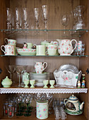 Glasses and vintage-style crockery in cupboard decorated with lace trim