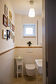 Gallery of pictures on wall and half-height tiling in small bathroom