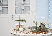 Bird food on cake stand, bird cage and decorations on rusty metal table