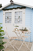 Vintage-style metal garden furniture outside pale blue summer house