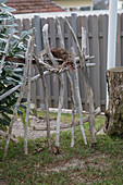Wreath on DIY garden fence made from weathered branches