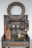 Wicker wreath and wintry decorations on rustic potting table
