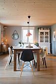 Verschiedene Stühle am Holztisch im Esszimmer im modernen Landhaus
