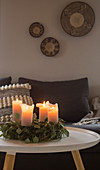 Advent wreath with lit candles in grey living room